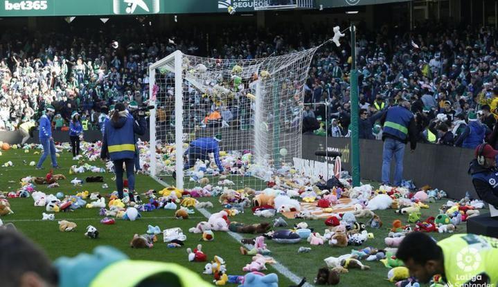 Un bonito detalle en Navidad : los aficionados del Betis tiran miles de peluches al césped para regalárselos a los niños desfavorecidos