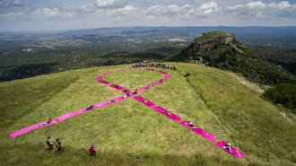 Los viajeros instalan un lazo gigante rosa en las Tetas de Viana en solidaridad con el cáncer de mama